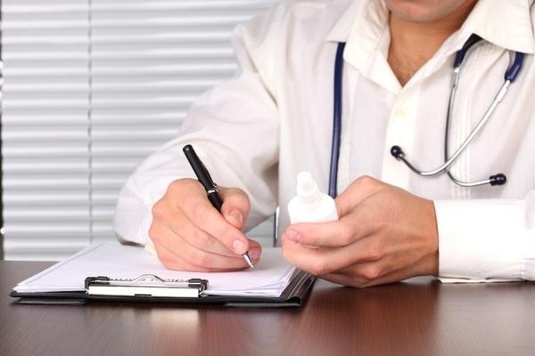врач пишет на бумаге