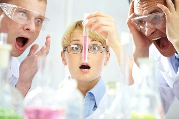 трое учёных смотрят на пробирку
