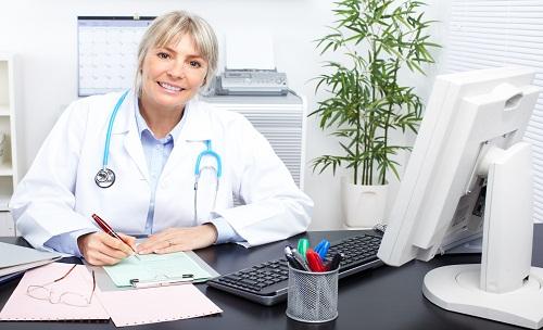 врач пишет за столом